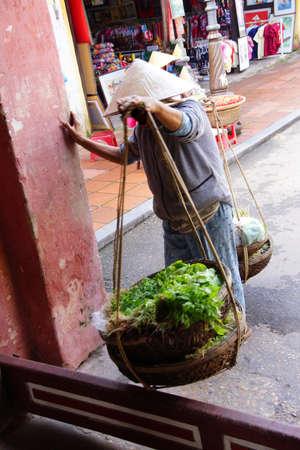 Vietnamese  woman carrying fresh vegetables and baskets,   Hoi An, Vietnam Stock Photo