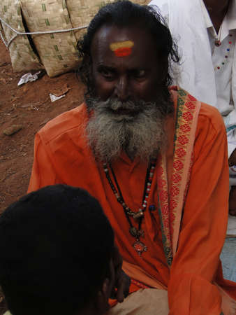 ORISSA, INDIA - NOV 13, 2009 - Sadhu gives advice  on market day , in Orissa, India Editorial