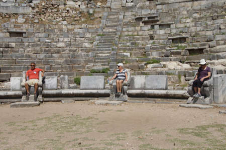 PRIENE, TURKEY - MAY 26, 2014 - Tourists occupy the best seats in the  ancient theater,  Priene,  Turkey