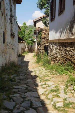 Bare stone and whitewashed walls on narrow street in Sirince, Turkey
