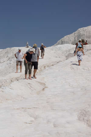 PAMUKKALE, TURKEY - MAY 27, 2014 - Tourists descend the  travertine turquoise  terraces at  Pamukkale,  Turkey Редакционное