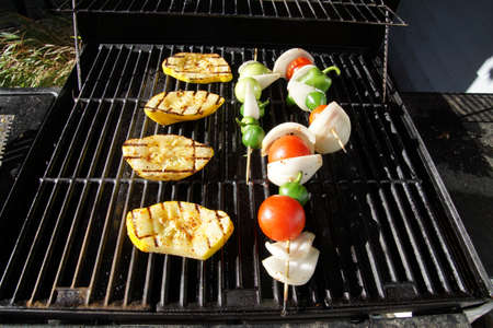 Yellow squash tomato and onion on the grill on a summer day in Seattle, Washington Фото со стока