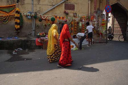 JAIPUR, INDIA - 8 oktober 2017 - Vrouwen in kleurrijke sari's lopen voorbij Divali bloemenverkopers in Jaipur, Rajasthan, India Stockfoto - 87374150