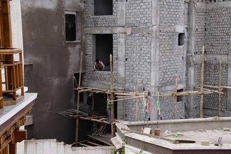 Workmen on construction scaffolding, Leh, Ladakh, India