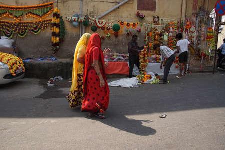JAIPUR, INDIA - 8 oktober 2017 - Vrouwen in kleurrijke sari's lopen voorbij Divali bloemenverkopers in Jaipur, Rajasthan, India Stockfoto - 87374220