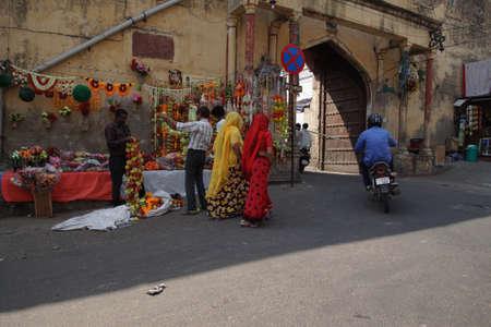 JAIPUR, INDIA - 8 oktober 2017 - Vrouwen in kleurrijke sari's lopen voorbij Divali bloemenverkopers in Jaipur, Rajasthan, India