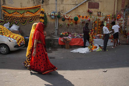 JAIPUR, INDIA - 8 oktober 2017 - Vrouwen in kleurrijke sari's lopen voorbij Divali bloemenverkopers in Jaipur, Rajasthan, India Stockfoto - 87374162