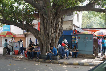 NEW DELHI, INDIA - SEP 10, 2017 - Young men stop for tea under a banyan fig tree in New Delhi, India