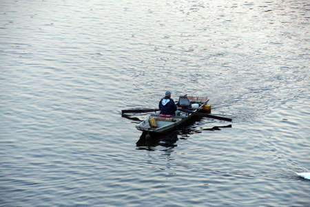 Fisherman in rowboat on the Vltava river in early morning  Prague, Czech Republic