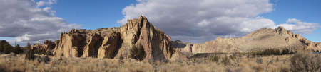 panorama of Monument and other jagged peaks  along the Crooked River at Smith Rock State Park, Oregon Stock Photo