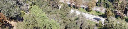 Tráfico en la autopista a través del cañón verde en San Diego, California Foto de archivo - 91735907