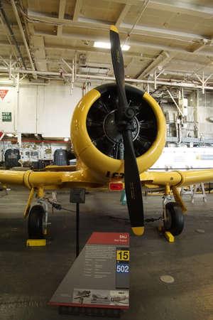 SAN DIEGO, CALIFORNIA - DEC 1, 2017 - SNJ  Trainer airplane on hangar deck of USS Midway CV-41 Aircraft Carrier, San Diego, California Editorial