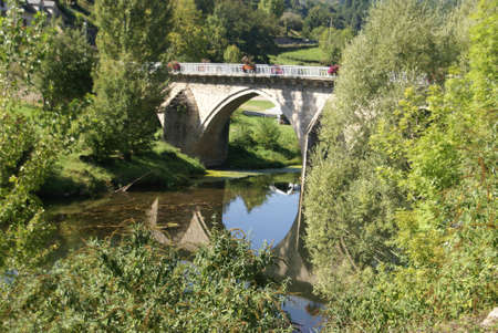 Arched stone bridge over river  near Entraygues, France  Stock Photo