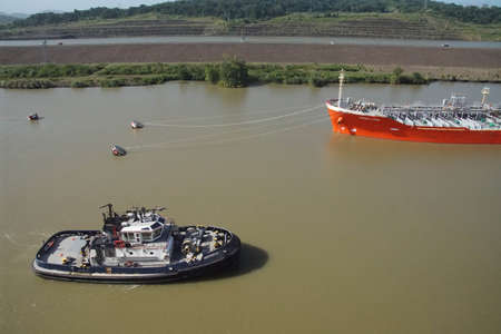 PANAMA CANAL - DEC 16, 2017 - Tug boat and freighter in transit between locks of the Panama Canal