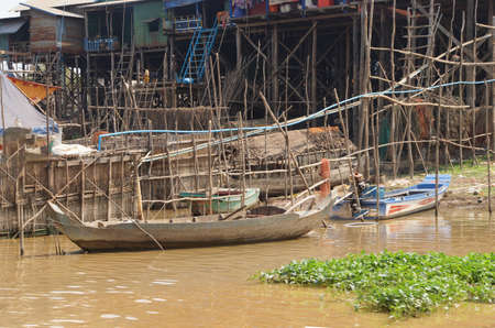 Stilt houses and boats during dry season at the Kompong Kleang floating fishing village,  Cambodia 免版税图像