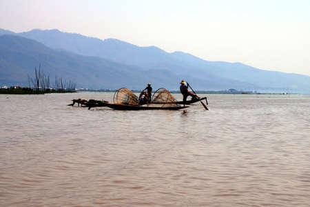 脚の漕ぎ漁師は、インレー湖、ミャンマー(ビルマ)で彼の小さなボートを推進します 写真素材 - 93763679