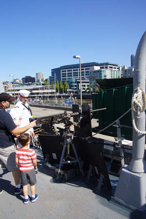 SEATTLE - AUG 4, 2016 - Sailor explains the heavy machine gun to visitors aboard the USS Gridley  (DDG 101) guided missile destroyer, docked in Seattle for Fleet Week