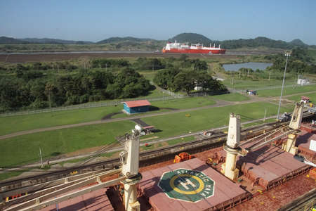 PANAMA CANAL - DEC 16, 2017 - Large freighter approaching San Miguel lock, with larger ship in new lock in the background, Panama Canal
