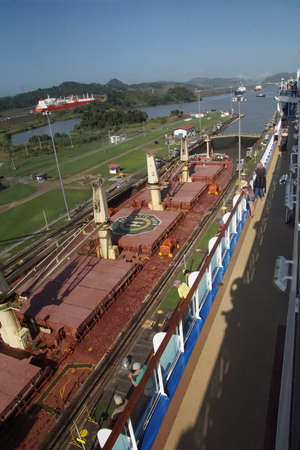 PANAMA CANAL - DEC 16, 2017 - Cruise ship passengers observe adjacent freighter passing through lock of the Panama Canal Redakční