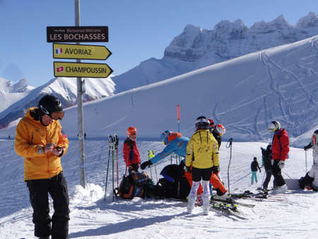 CHAMPOUSSIN, SWITZERLAND - FEB 13, 2018 -Directional signpost and skiers in alpine terrain in the Portes du Soleil near Champoussin, Switzerland