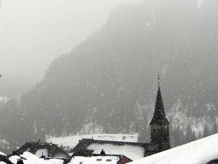 Snow covered church steeple with white conifer forest, Chatel, France
