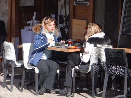 CHATEL, FRANCE - FEB 20, 2018 - Young women having lunch outdoors at a restaurant in small alpine village of Chatel, France Editöryel