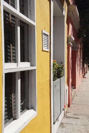 Yellow ochre colonial building with flowers, Cartagena, Colombia