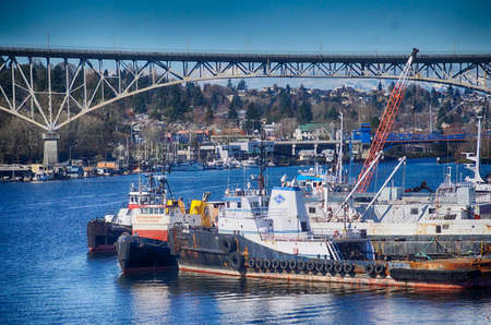 SEATTLE - MAR 11, 2018 - Fishing fleet docked on Lake Union with Aurora Bridge in background in Seattle, Washington
