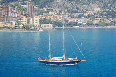 Sailboat motoring out of the harbor of Monte Carlo, Monaco
