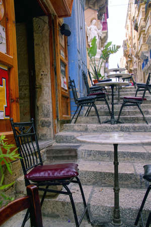 Tiny cafes with tables on stairs of narrow street,Valletta, Malta