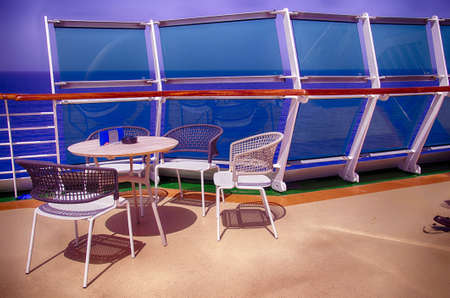 Table and chairs on outside deck on a cruise ship in the Mediterranean Sea