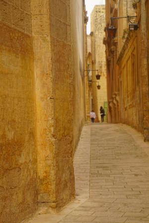 Narrow street with high limestone walls in Mdina, Malta