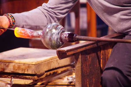 Glass blower turning heated glass to form a vase in a factory in Murano Venice, Italy
