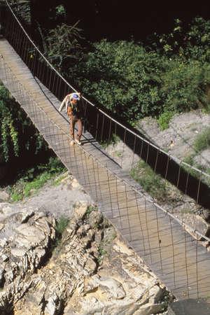 POKHARA, NEPAL - DEC 2, 1987 - Crossing a suspension bridge over the Kali Gandaki river, Himalaya,Nepal