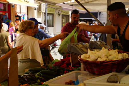 LIVORNO, ITALY - APR 23, 2018 - Shoppers buying fresh fruit in the market of Livorno, Italy Editorial