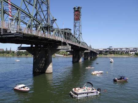 PORTLAND, OREGON - JUL 5, 2018 - Pleasure boats on the Willamette River float under the Hawthorne Bridge in  Portland, Oregon