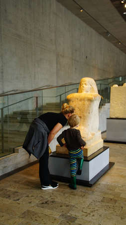 MUNICH - JUL 21, 2018 - Mother and child examine a statue in the Egyptian Museum, Munich, Germany Editöryel