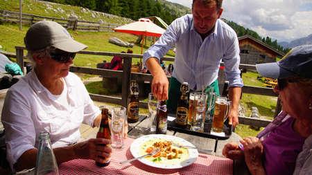 DOLOMITES, ITALY - JUL 29, 2018 - Waiter delivers drinks at alpine hut Berghause Platzwiese - Albergo  Prato Piazza, Dolomites Alps, Italy Redactioneel