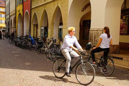 BOLZANO, ITALY - JUL 26, 2018 - Bicyclist on  the narrow cobbled street of Bolzano, Italy 報道画像
