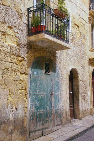 Vintage door and balcony on narrow street of Valletta, Malta