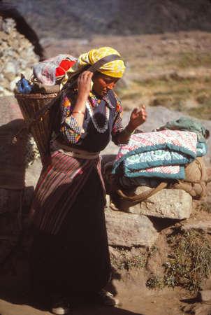 SUN KOSI, NEPAL - DEC 10, 1979 -Sherpani carrying a load on a trek in Rowaling Himalaya, Nepal, Asia