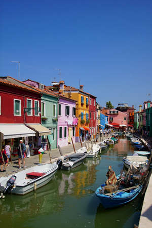 VENICE, ITALY - AUG 11, 2018 - Tourists on a canal with brightly painted houses in Burano Island, Venice, Italy 에디토리얼