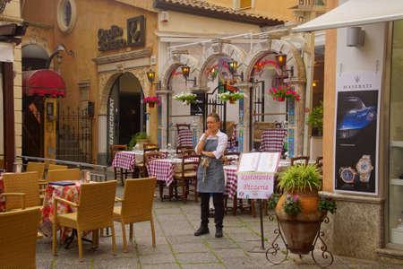 TAORMINA, ITALY- APR 18, 2018 - Waitress outside her restaurant in Taormina Sicily, Italy