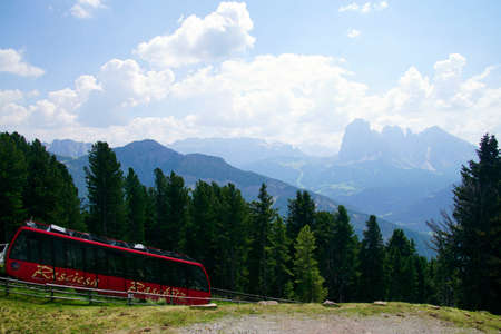 ORTESEI, ITALY - AUG 5, 2018 - Alpine funicular train approaches the upper terminal in the Dolomites Alps, Italy