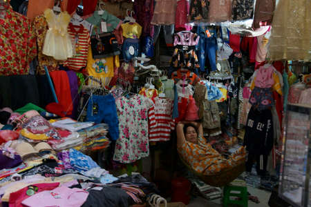 KRATIE, CAMBODIA - FEB 10, 2015 - Vendors sell clothing from their stall in the central market of  Kratie, Cambodia Redactioneel