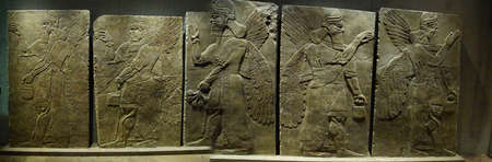 MUNICH - JUL 21, 2018 - WInged and bearded genies with various attributes, Assyrian bas relief, Egyptian Museum, Munich, Germany
