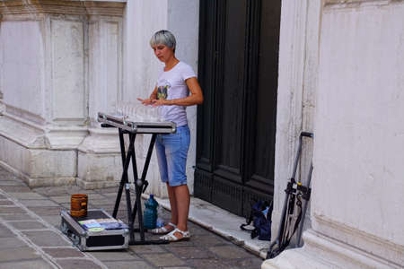 VENICE, ITALY - AUG 10, 2018 - Female busker playing the glass harmonica in Venice, Italy