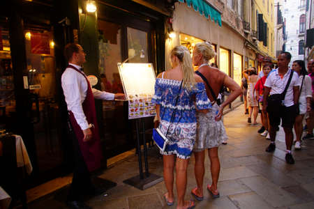 VENICE, ITALY - AUG 10, 2018 - Young women check the menu outside a restaurant in Venice, Italy Editorial