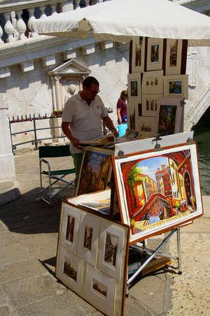 VENICE, ITALY - AUG 10, 2018 - Artist displays his paintings near the Rialto bridge in Venice, Italy