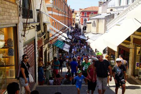VENICE, ITALY - AUG 10, 2018 - Crowd of tourists crosses the Rialto Bridge in Venice, Italy Editorial